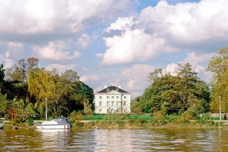A grand 1700s white house on a riverbank against a cloudy sky