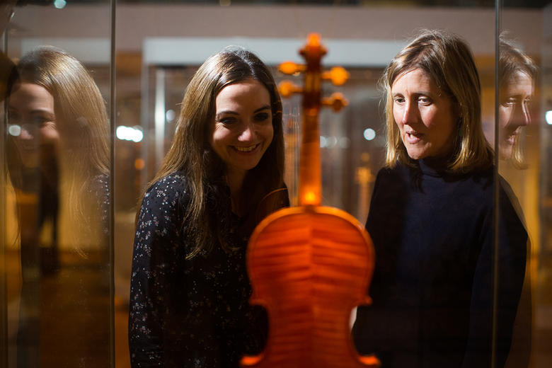 Two women look at a Stradivarius violin in the music gallery