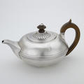 A silver teapot with wooden handle