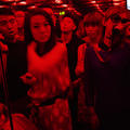 A soft-focus, red-hued photograph of a crowd of people in an indoor space