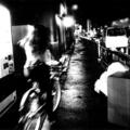A dark, black and white photo of a woman riding a bicycle