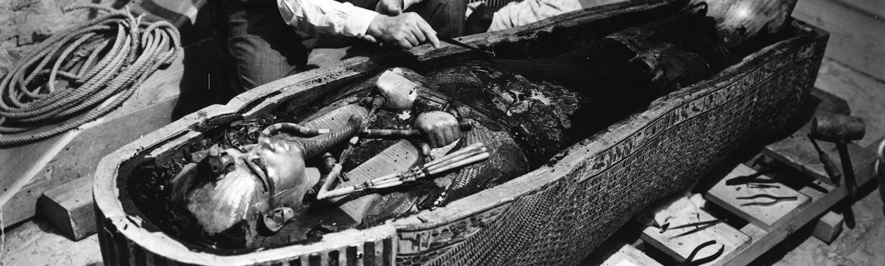 Black and white photograph of two people looking a Mummy in a Coffin