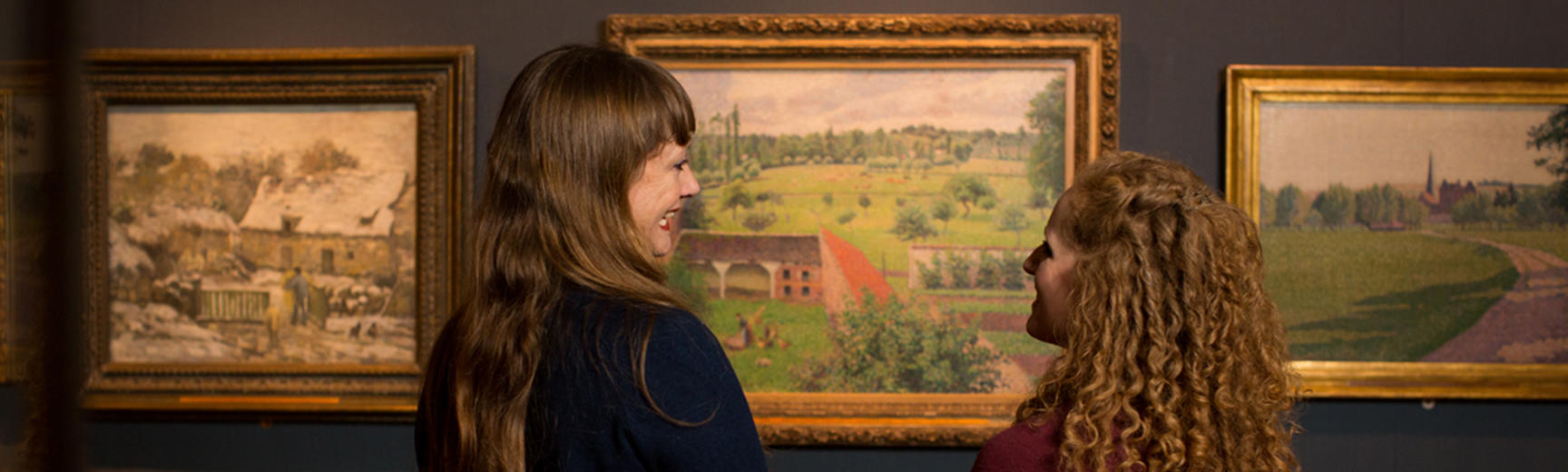 Two women looking at a Pissarro painting