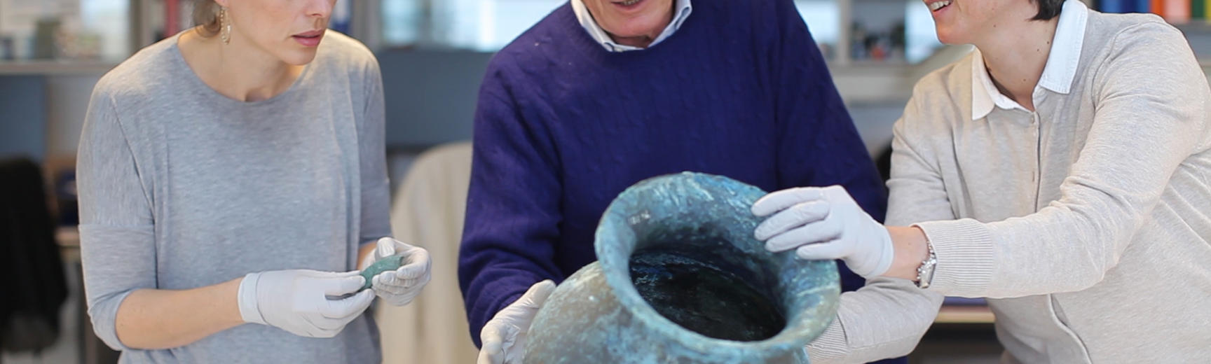 Three conservators looking at a pot from Pompeii