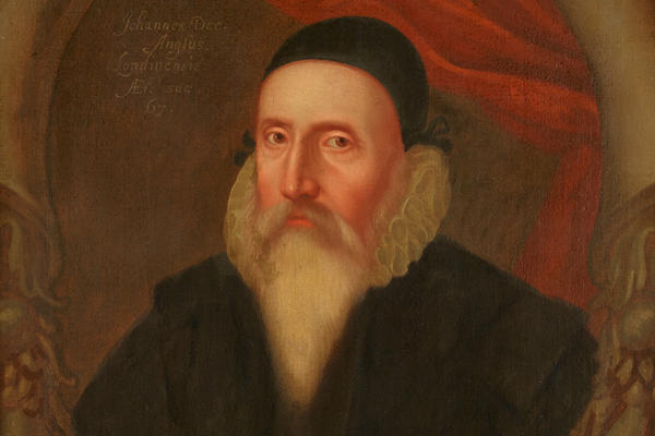 Painted portrait of John Dee who wears a black cap and a long white beard