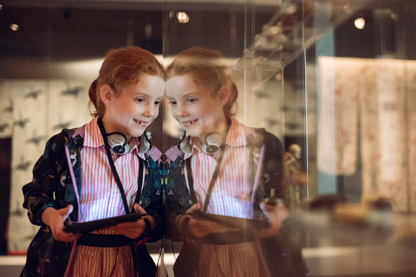 A smiling girl holds a multimedia guide and looks into a glass museum case