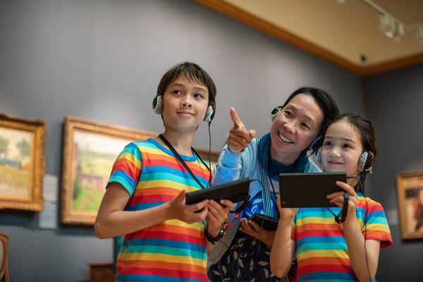 Two children in rainbow t-shirts, and a woman, smile as they use multimedia guides in a museum gallery