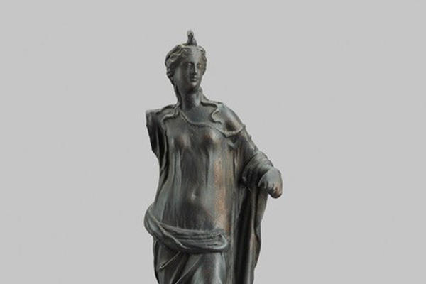 A tall metal statuette of a woman