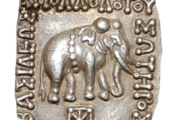 A square silver coin with an engraving of an elephant and scripture around the edges of the coin