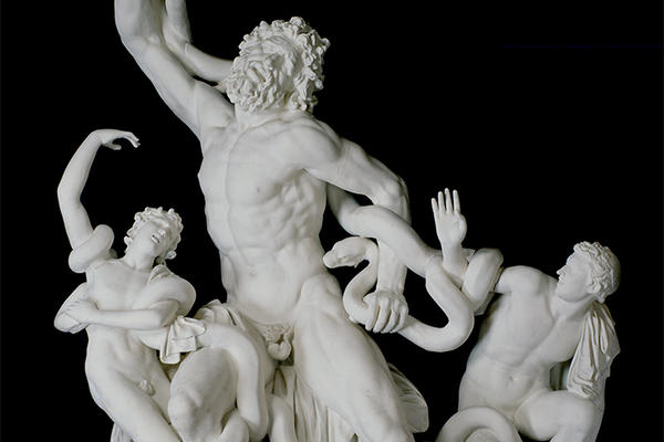 White cast sculpture of three male figure wrestling snakes, on a black background