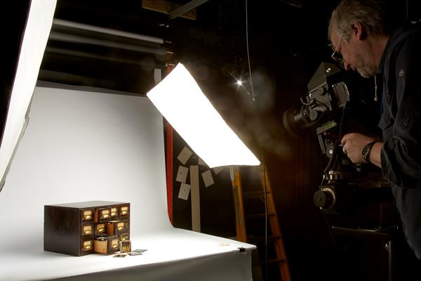 Staff member in the process of photographing an small antique drawers