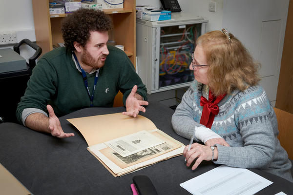 Two staff members digitising a work on paper