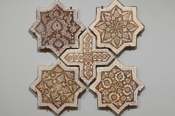 A photo of five brown tessellation tiles fitted into each other to form a pattern with a cross at the centre and four eight point stars around the edge.