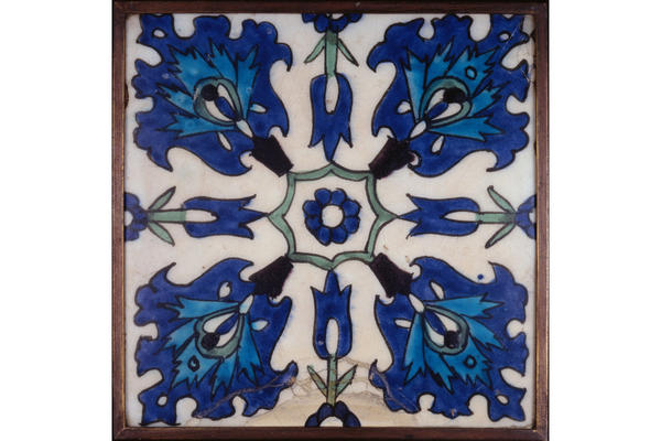 A square tile decorated with blue and green flowers.
