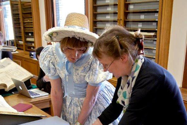 Image of Print Room Manager and a lady in a pale blue and white dress with straw hat looking at and discussing a piece of printed artwork