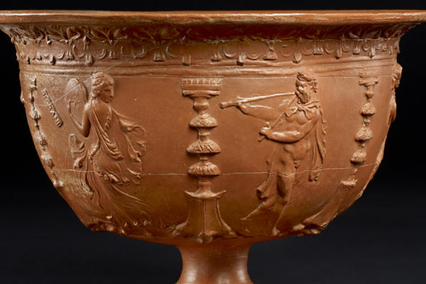 Red bowl decorated with musicians and dancers entertaining while servants bring food to banquet.