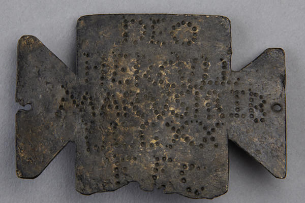 A bronze tablet with a punch dot inscription.