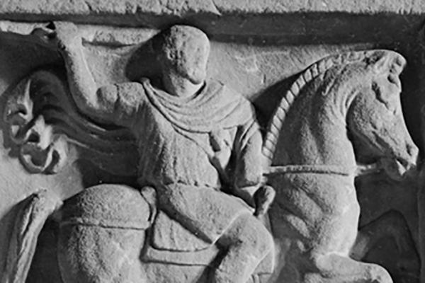 Detail of man riding horse on stone carving for grave monument