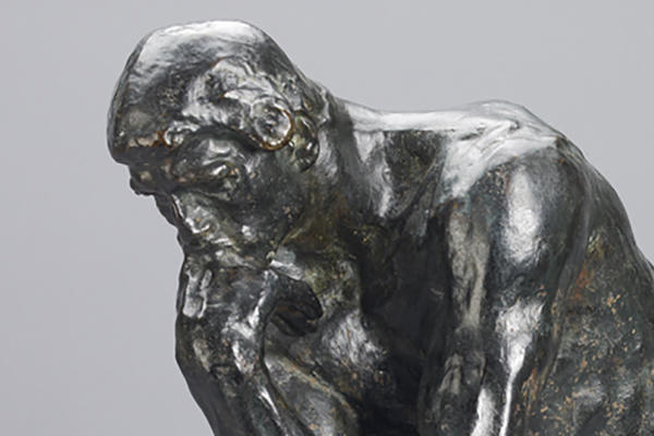 A bronze man sat down in a thinking position