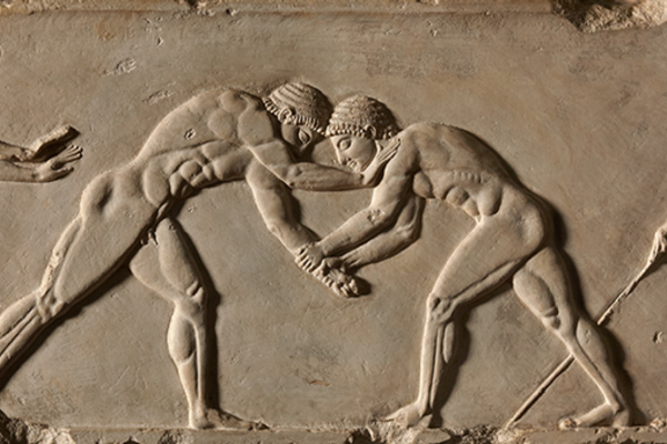 Stone relief of two men wrestling, with athletes either side