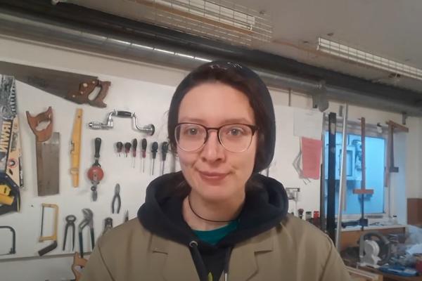 A woman speaks to a webcam from a technician's workshop