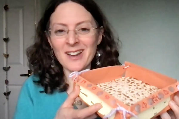 A still from a video showing a woman holds up a homemade basket