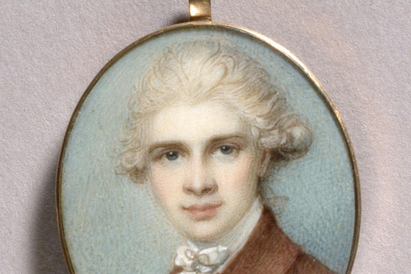 A small enamelled roundel with a portrait of a young man in white wig against a blue background.