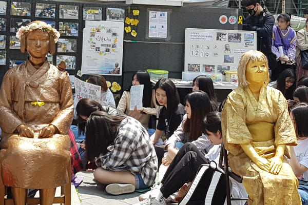 A lady dressed in a gold-coloured traditional kimono and facemask, sat on a stool outdoors next to a bronze-coloured life-size seated statue, surrounded by members of the public