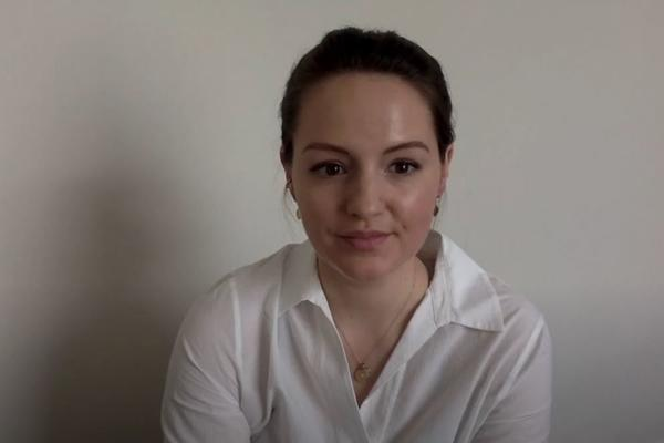 A young woman speaks to a webcam, with a white background