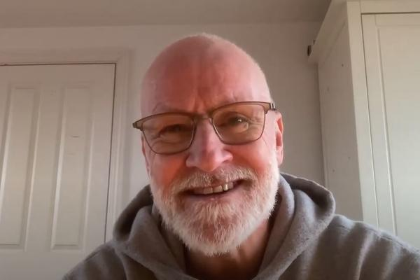 A man with beard and glasses speaks to a webcam, with a white background