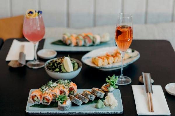 View of a table set with sushi, drinks and chopsticks