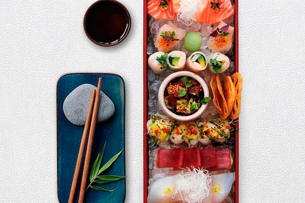 View from above of a selection of sushi alongside chopsticks and a bowl of soy sauce