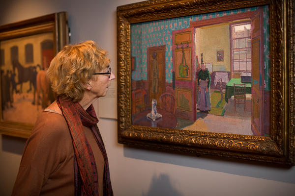 A woman looks at a painting by Sickert