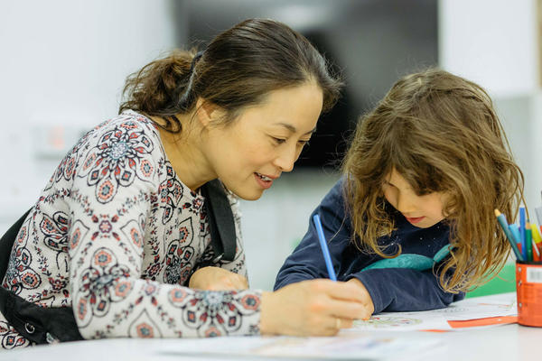 An image of a lady enjoying craft activities with a young girl
