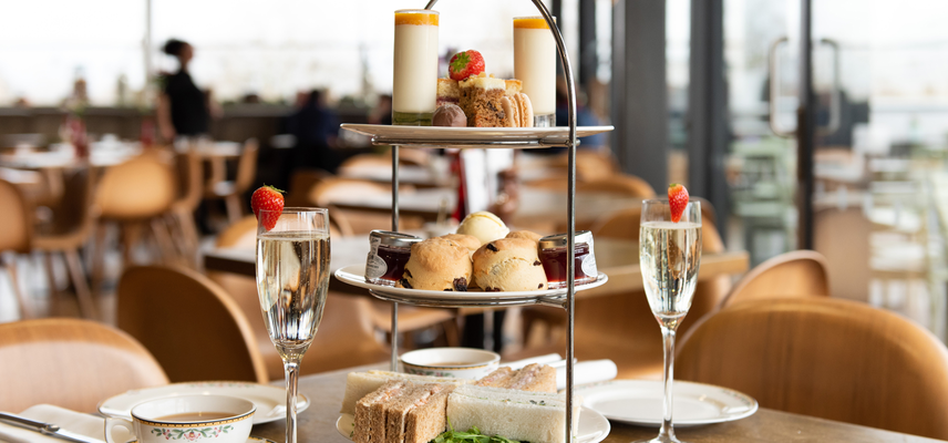 A tower of cakes and scones alongside teacups and glasses of prosecco