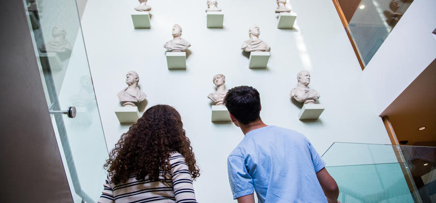 View from behind to museum visitors ascending a staircase, with busts on the wall in front of them