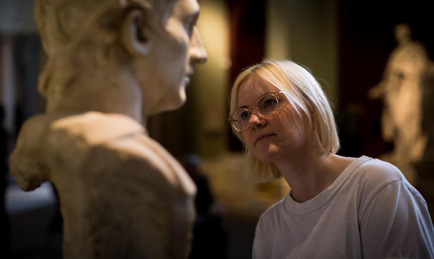 A woman looks closely at a bust