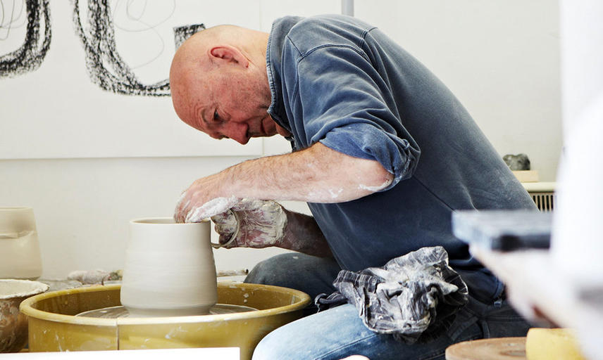 A man at a potters wheel making a vase