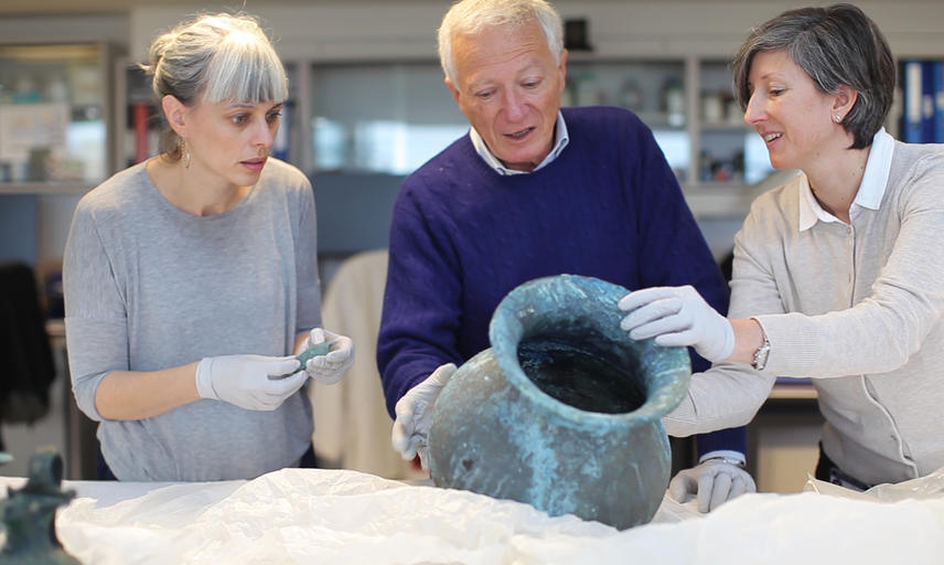 Three people looking at large pot wearing white gloves