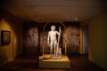 A life size statue of Bacchus standing in the middle of a gallery